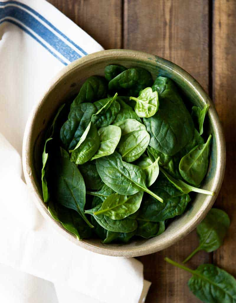 ceramic bowl filled with raw baby spinach leafy greens