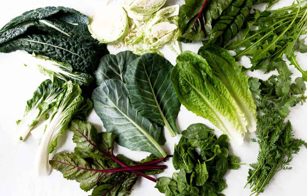 overhead shot of several different leafy greens, all of which you can be added to your next smoothie