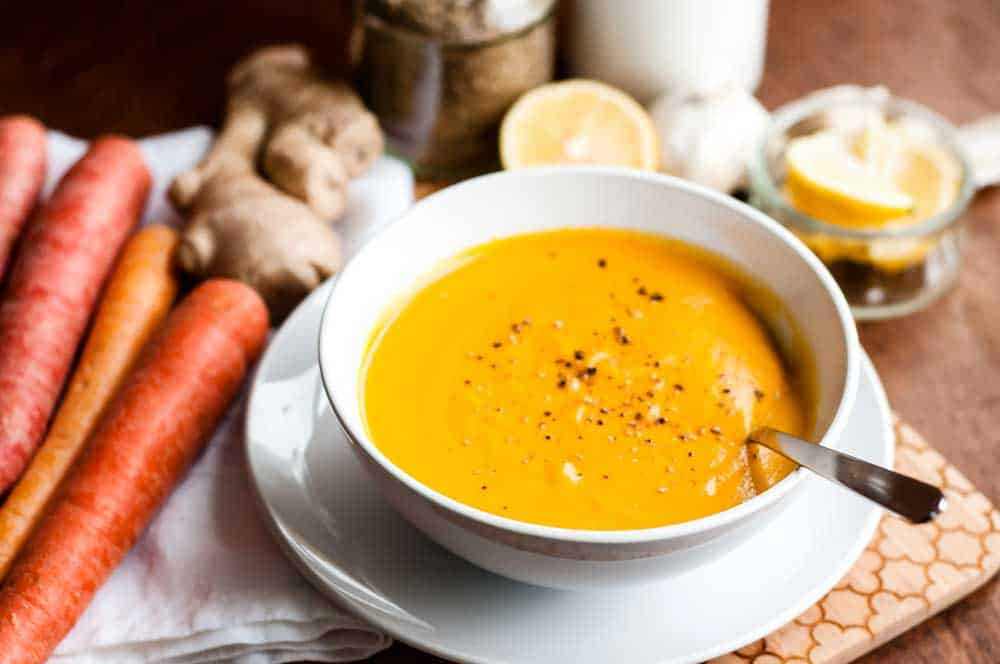 a vibrant bowl of carrot ginger soup with cracked pepper on top