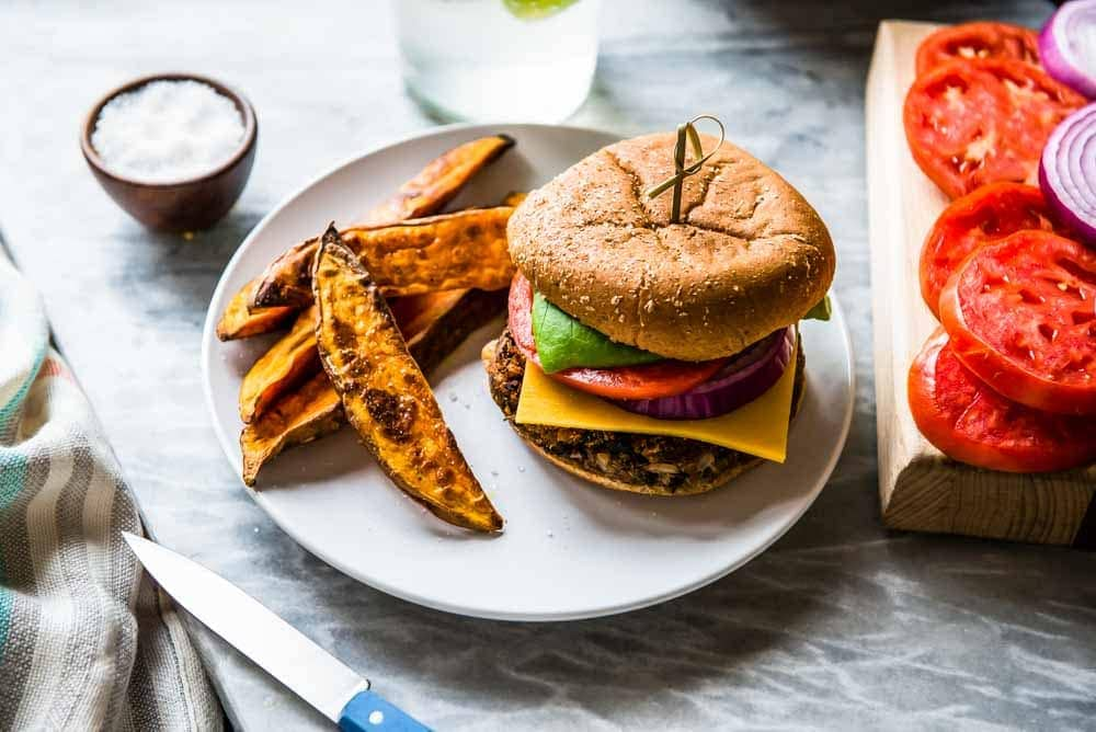 vegan black bean burger loaded with fresh toppings, a gluten free bun, and sweet potato wedges.