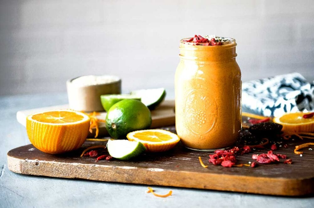 superfood smoothie on cutting board with whole ingredients surrounding it