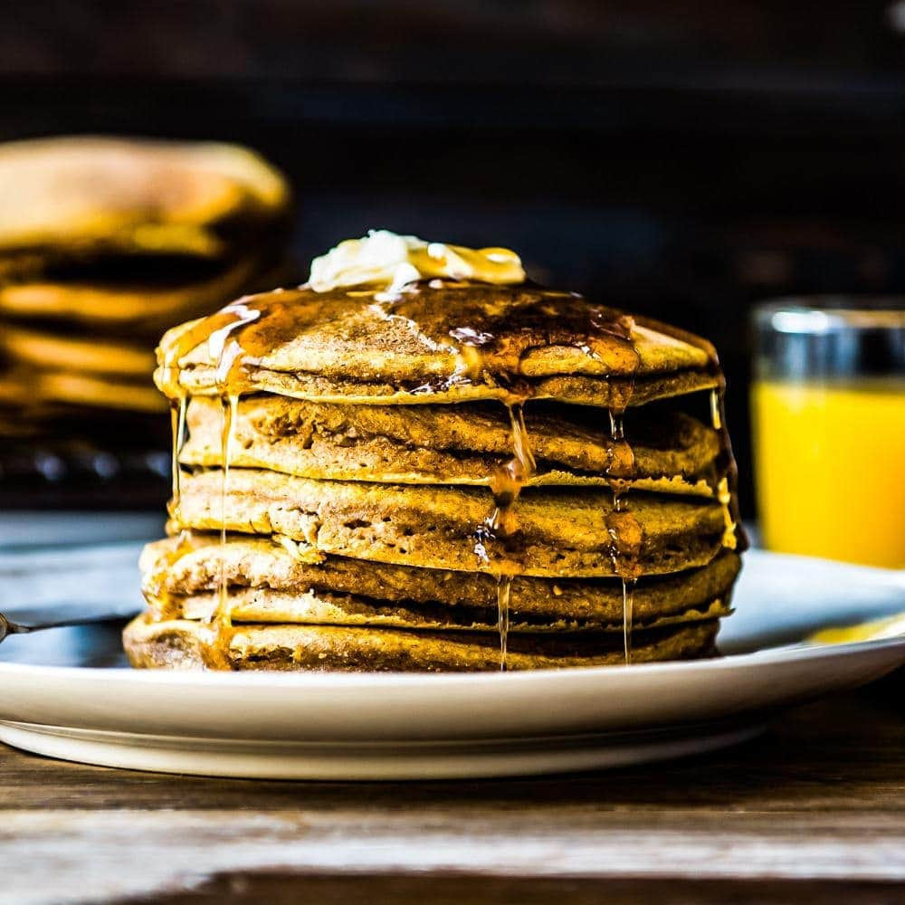 fresh stack of vegan pumpkin pancakes covered in syrup