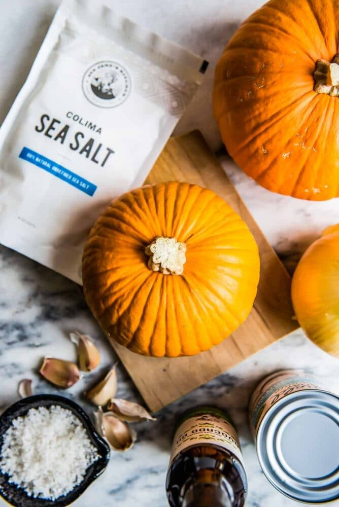 whole pie pumpkin next to a bag of Colima Sea Salt, ready to be roasted for this pumpkin soup