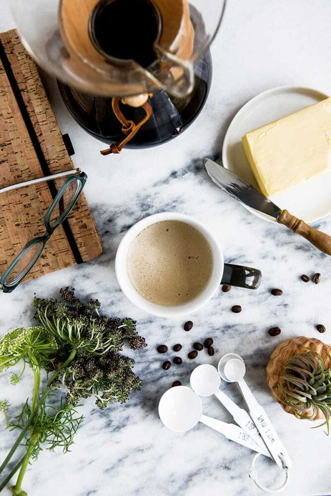 overhead shot of a cup of coffee, with a block of butter and a used butter knife, loose whole coffee beans, and greenery