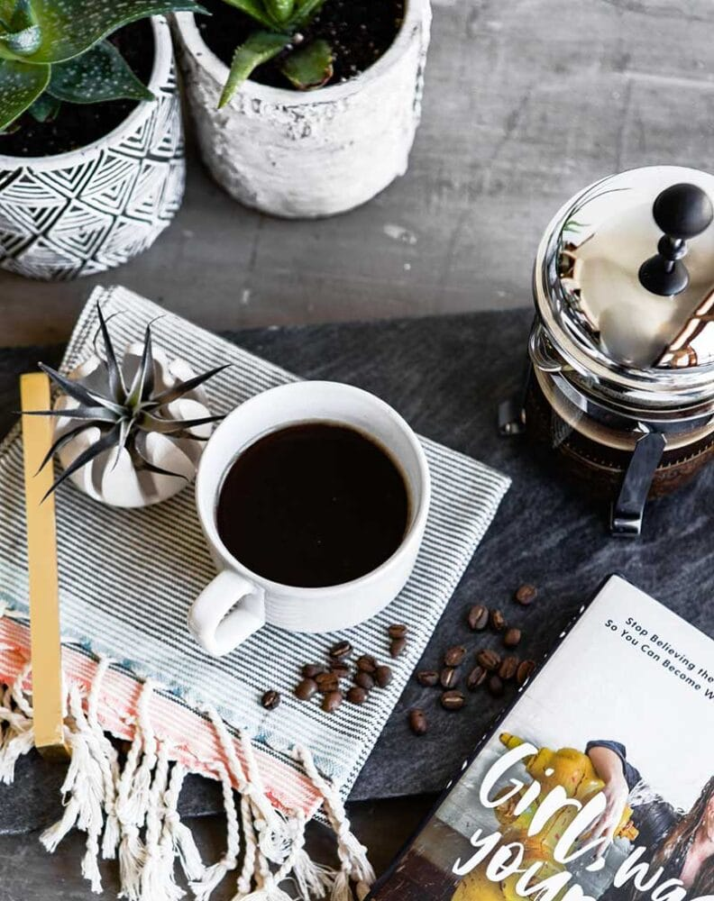 overhead shot of poured cup of healthy coffee, with french press, various succulents, and the corner of a book also seen