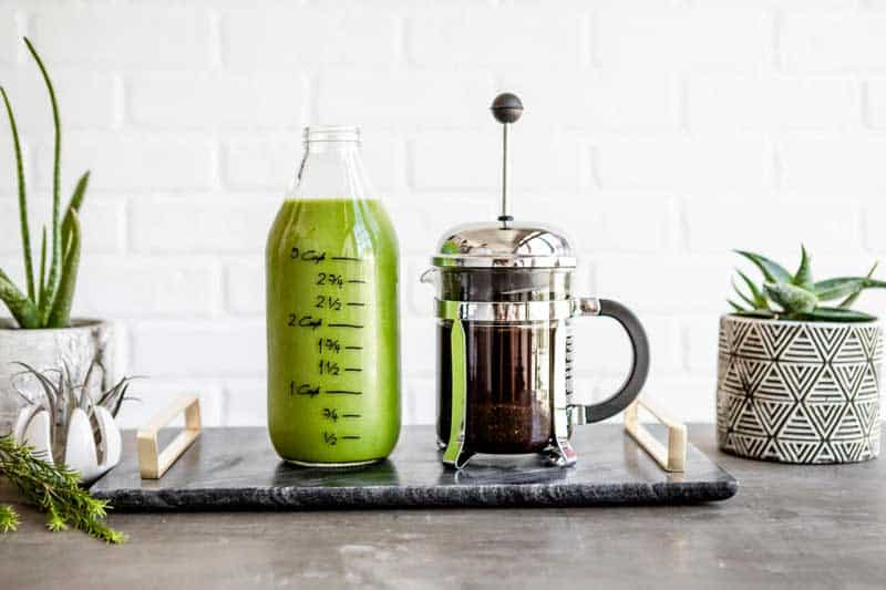 glass jug full of green smoothie next to a french press full of coffee on a marble slab