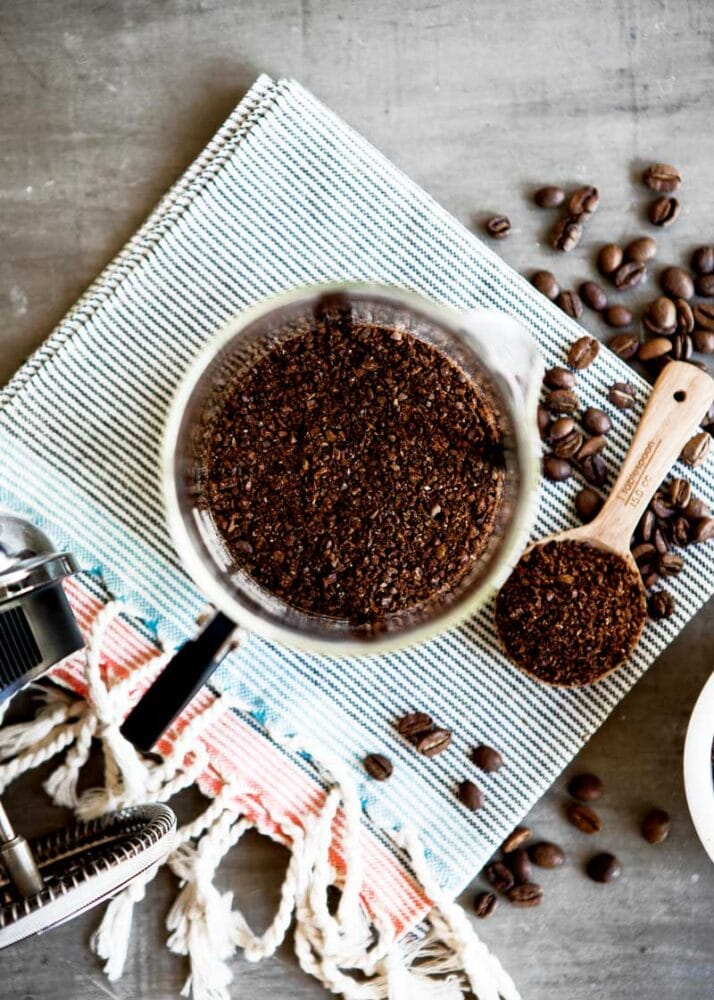 ground coffee close up on a spoon, with ground and whole bean coffee ready for a coffee recipe