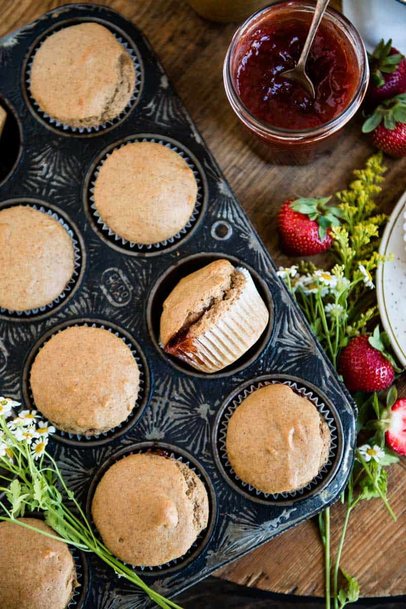 a pan full of strawberry jam-filled vegan muffins