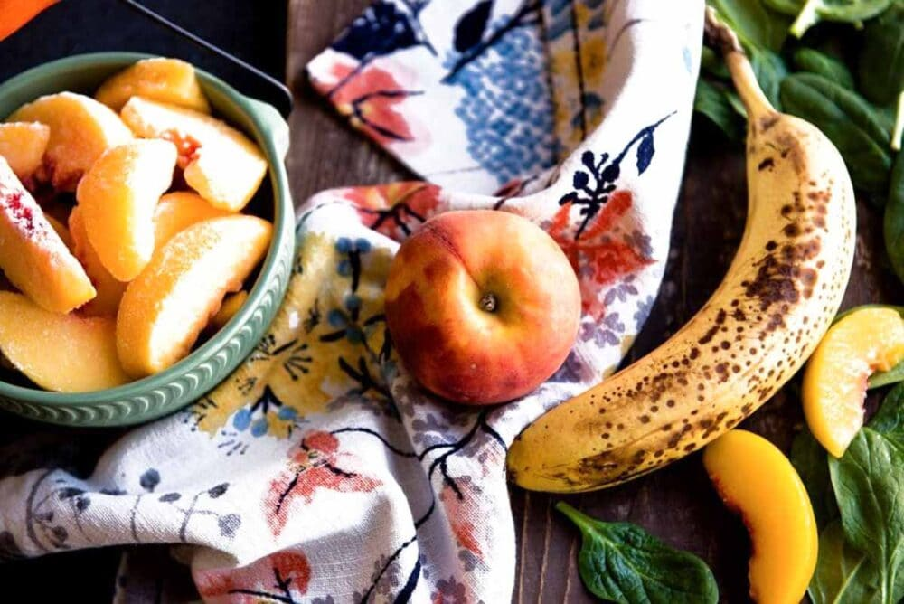 Ingredients for a vegan green smoothie with peach and banana