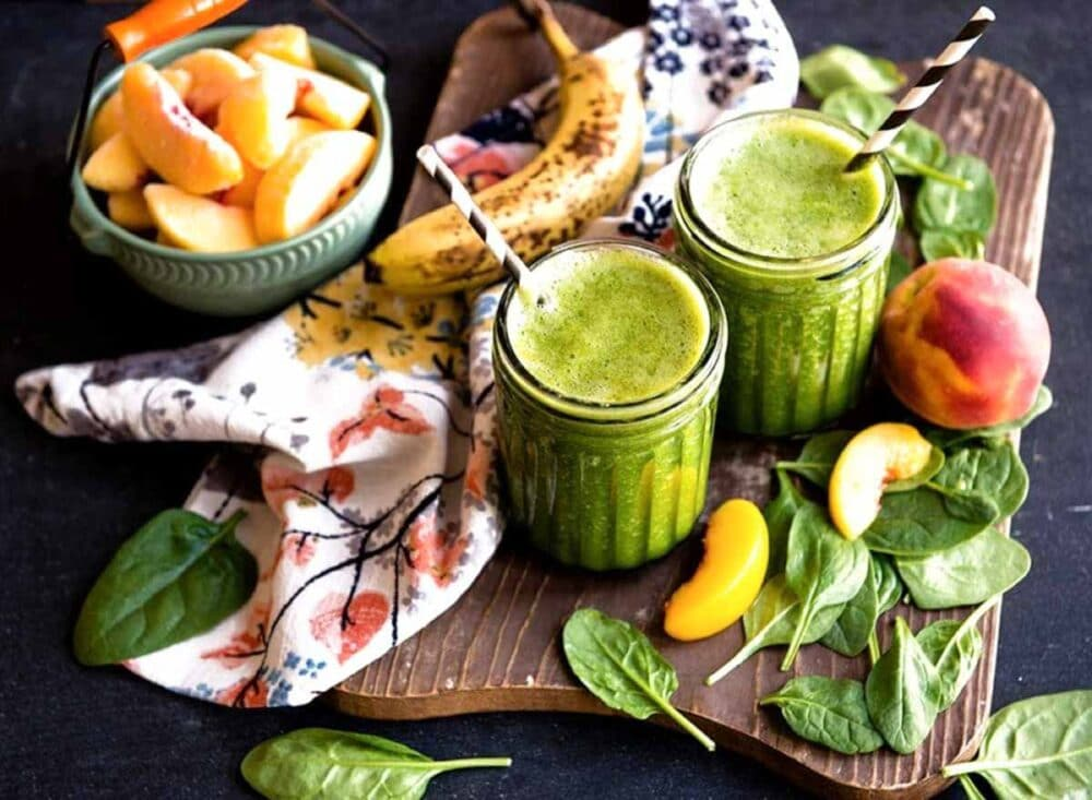 Green spinach, peaches and banana blended into sweet smoothie