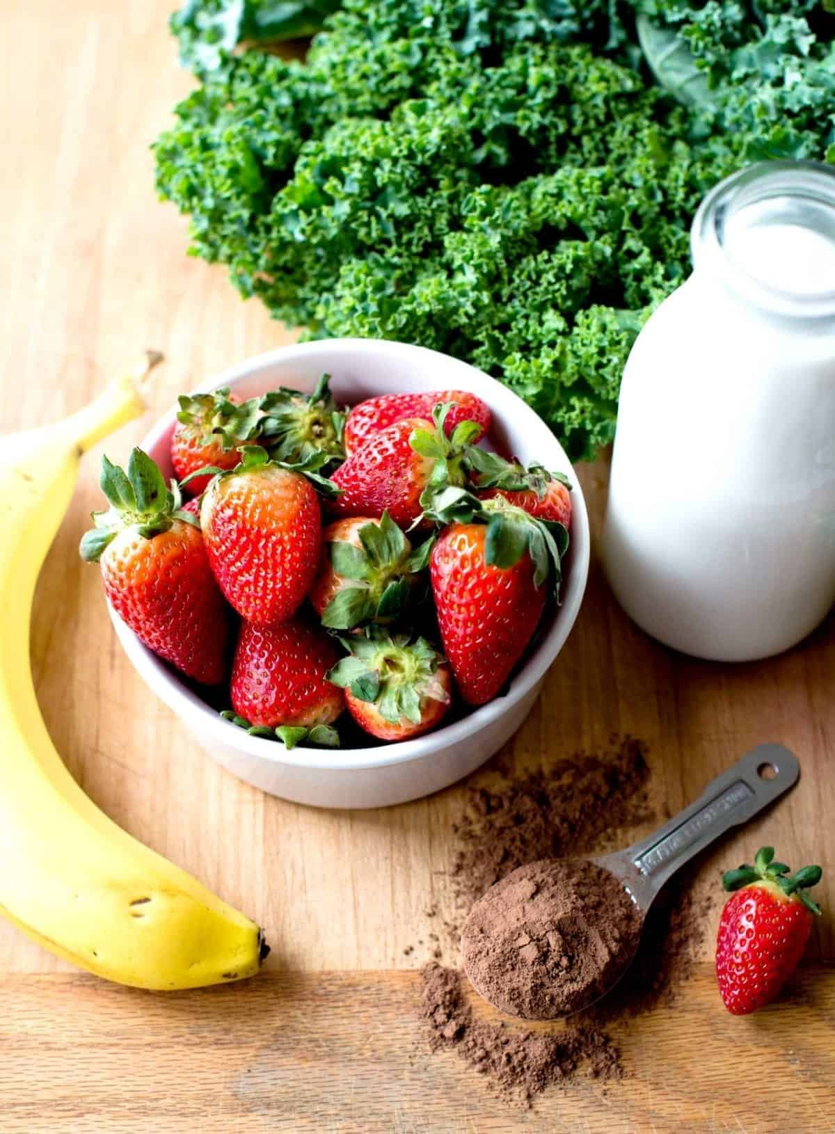 Strawberries, banana, milk, kale and cacao powder for smoothie