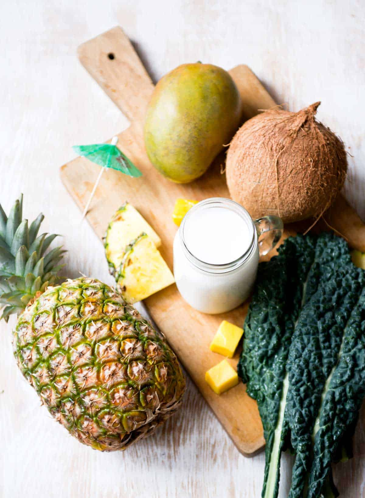 Kale, mango, coconut milk and pineapple to make a smoothie