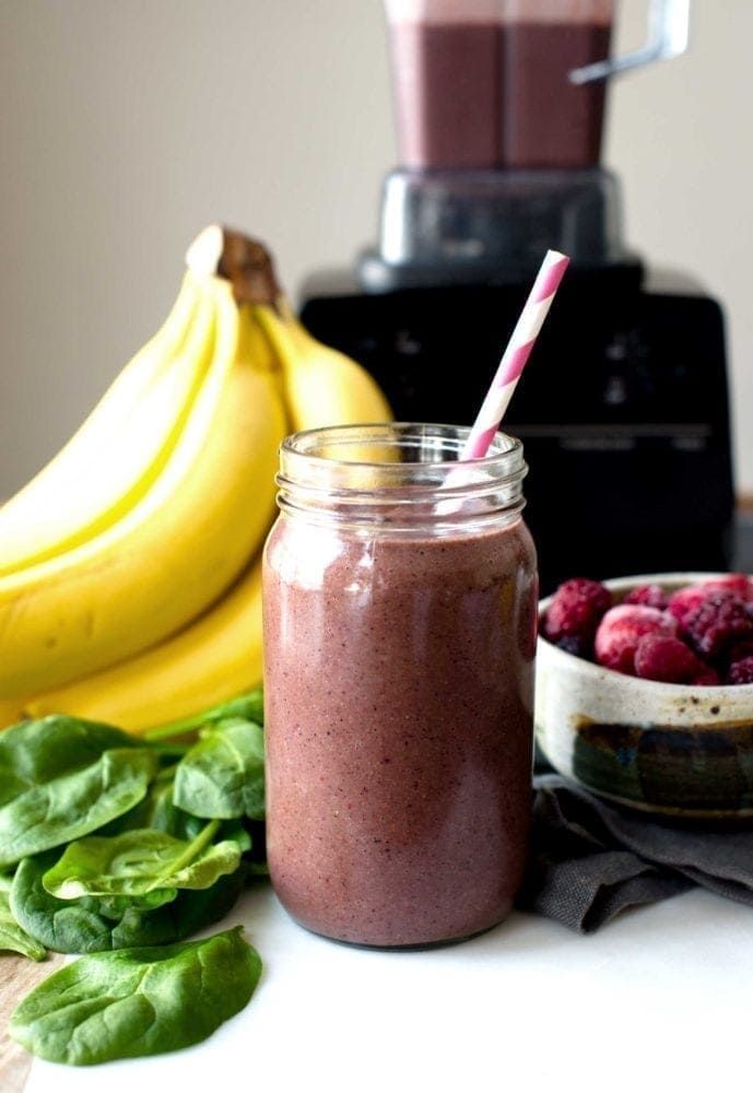 Healthy green smoothie with berries and spinach in mason jar with paper straw