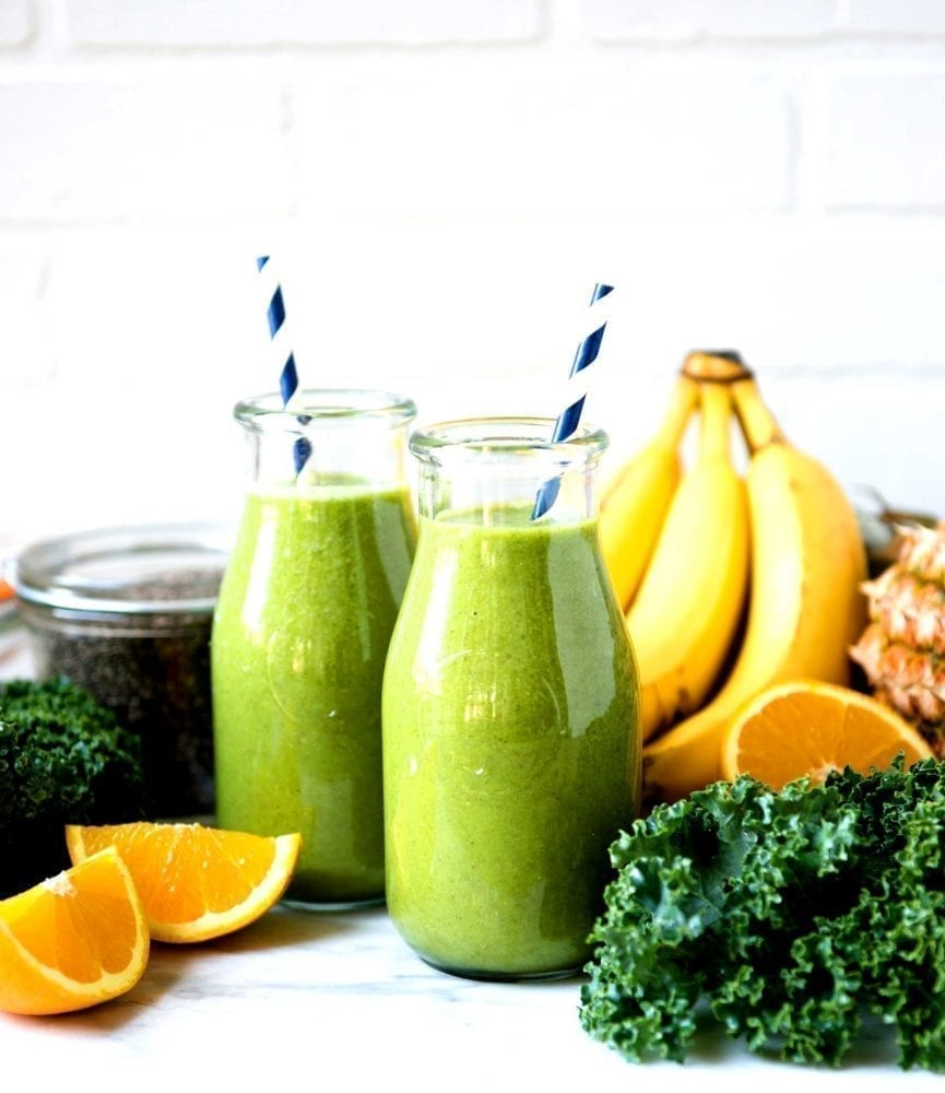 Old glass milk jugs used for a kale green smoothie using coconut water, oranges and banana.