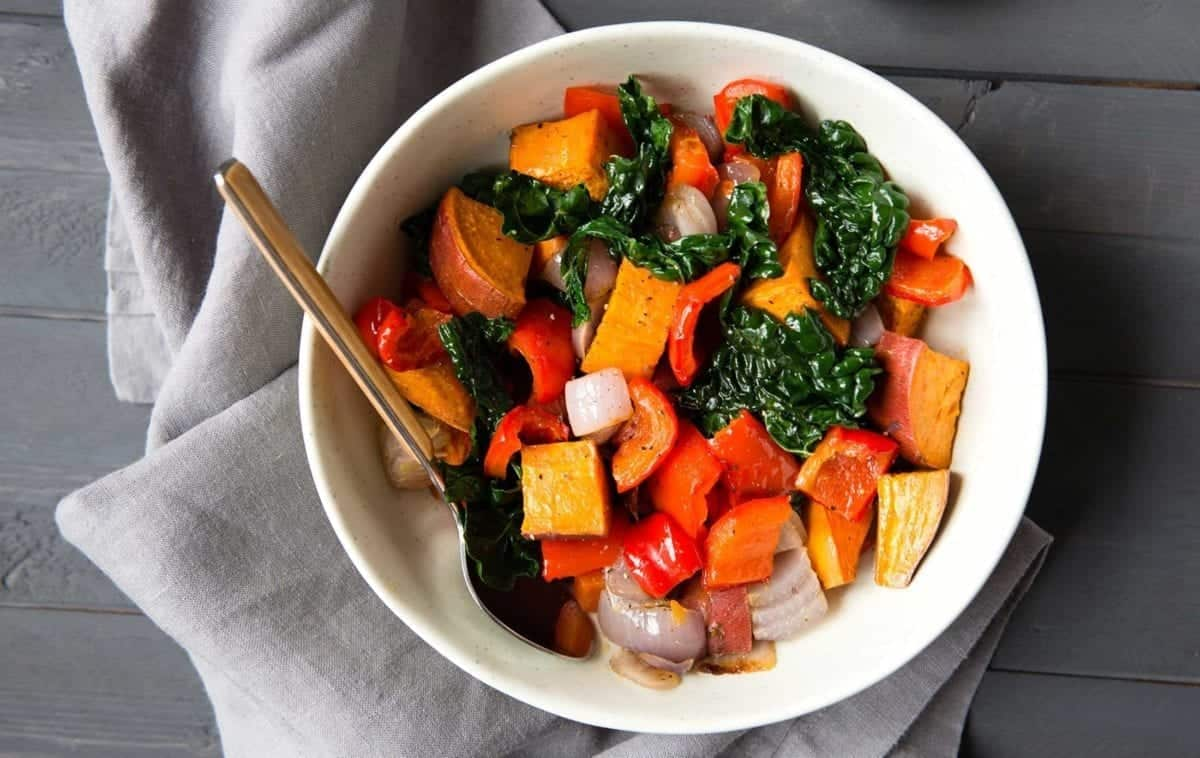white bowl full of colorful veggies with a spoon and napkin.