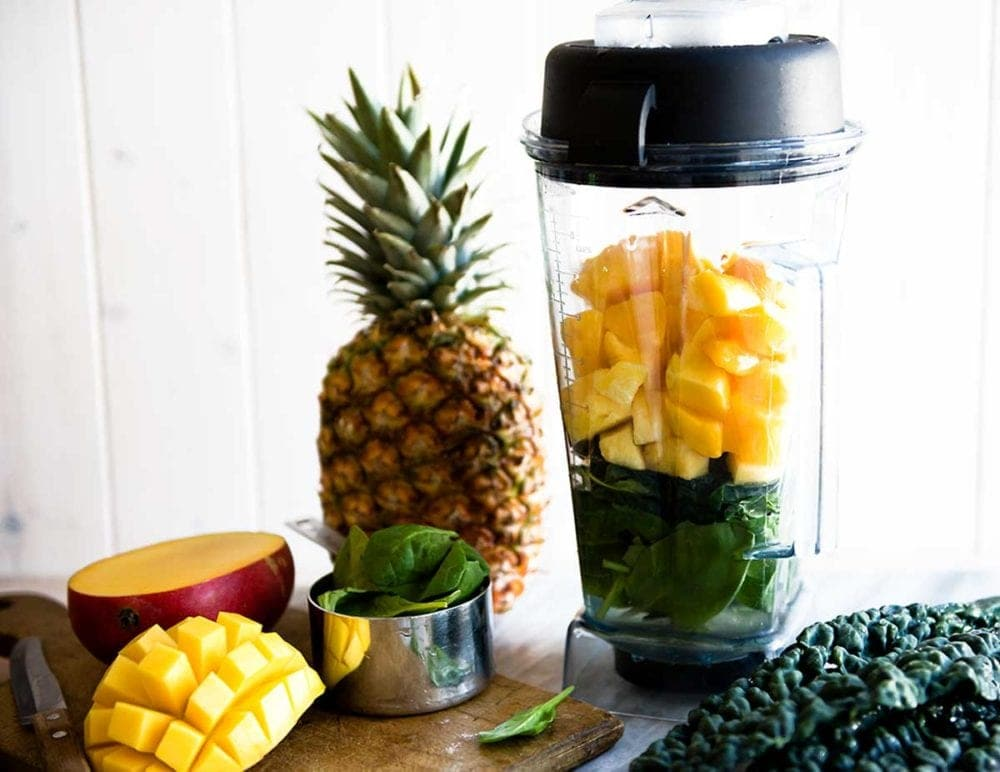 Vitamix blender loaded with fruits and spinach for a smoothie.
