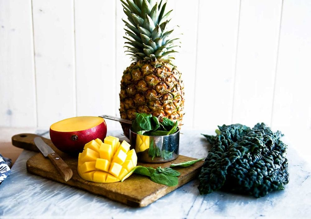 Kale, mango, pineapple and spinach on a cutting board for a smoothie.