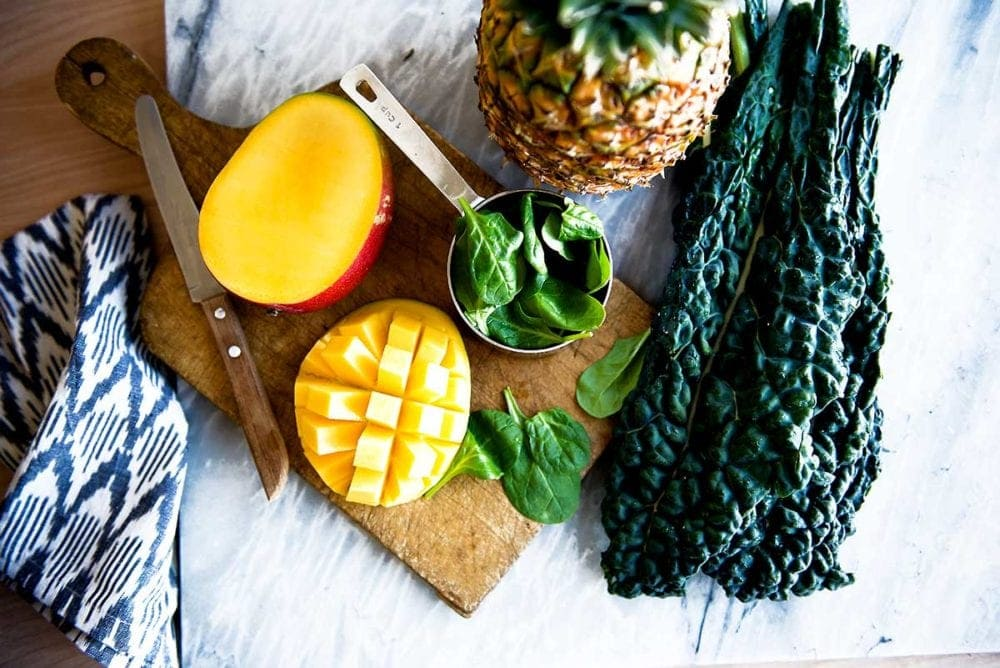 Plant-based whole food ingredients on a cutting board to prepare the smoothie recipe.