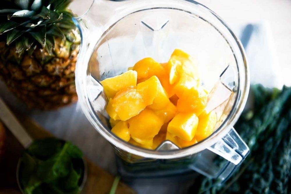 Frozen mango in a vitamix blender for a green detox smoothie.
