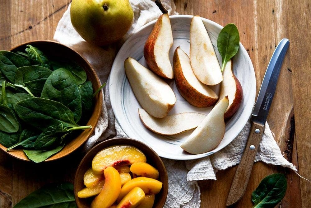 Sliced ripe pears on a plate with a knife and spinach to make a smoothie.
