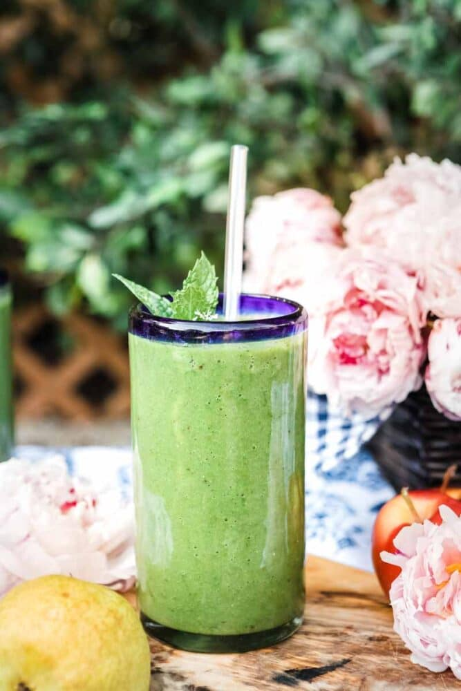 glass of glowing green smoothie with glass straw