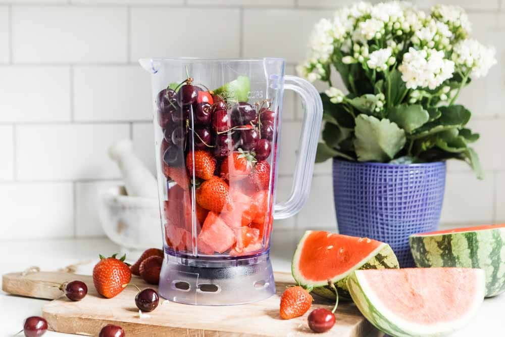 Blender filled with watermelon, cherries, strawberries and lime for smoothie