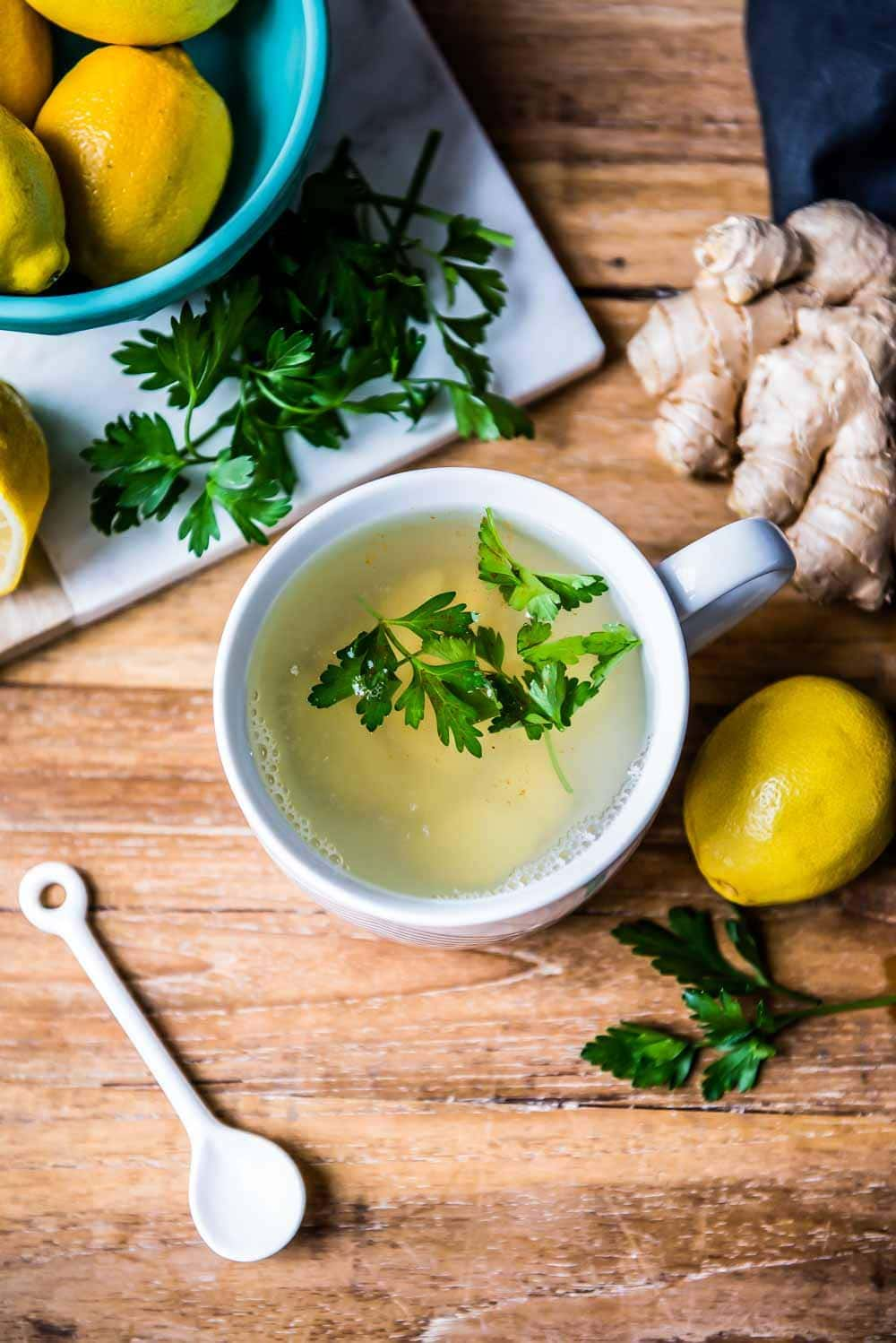overhead shot of the best detox tea recipe, complete with cleansing tea ingredients like lemon, ginger, and parsley