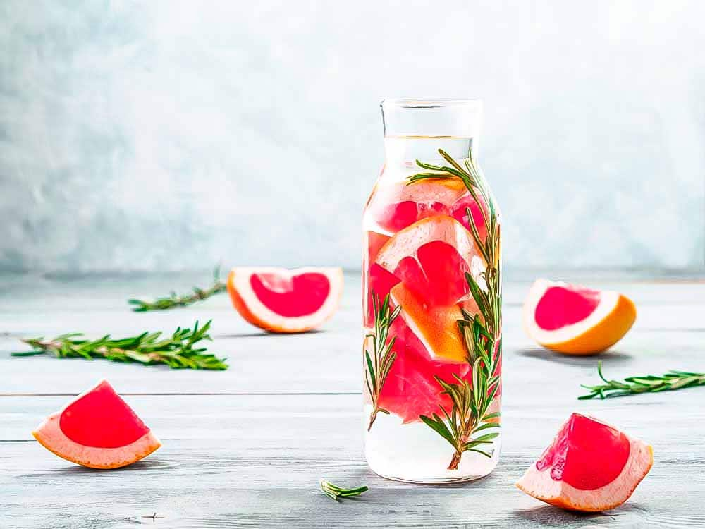 Sliced Grapefruit and rosemary in a glass to help the detox
