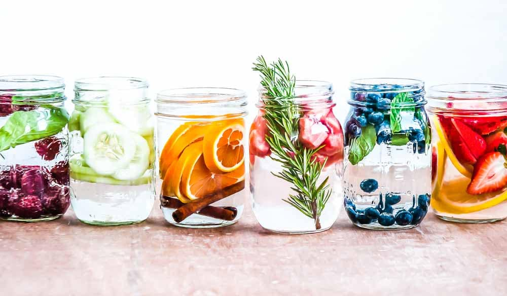 Mason jars filled with detox water in a row with berries, oranges, rosemary and grapefruiit