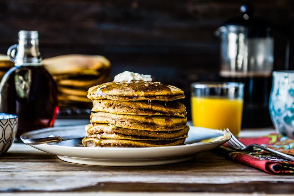 a stack of vegan pumpkin pancakes smothered in maple syrup