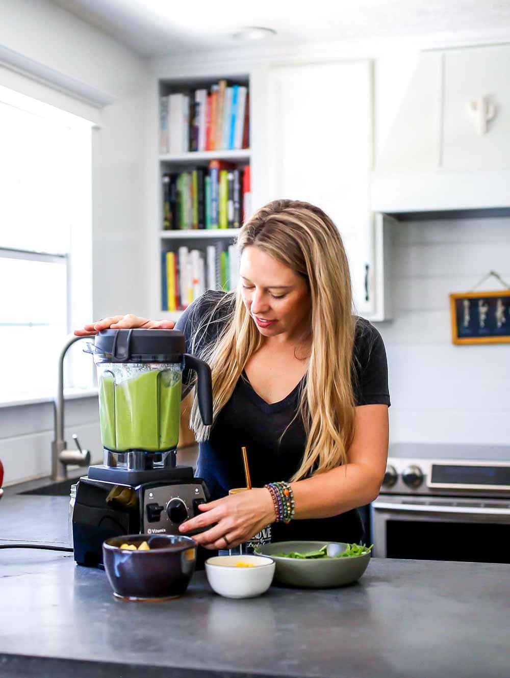 Blending a weight loss smoothie in the kitchen with spinach to help burn fat.