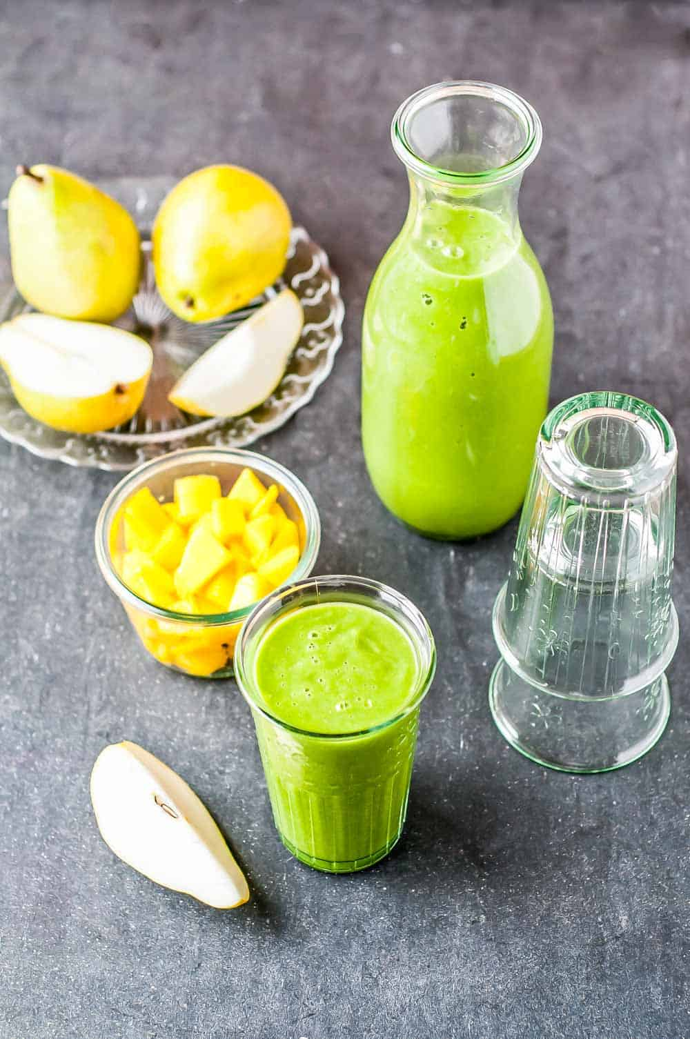 a tall glass of brain food smoothie along side sliced pears and pineapple. the best brain food list has 3 ingredients in this smoothie, hemp hearts, avocado, and spinach.