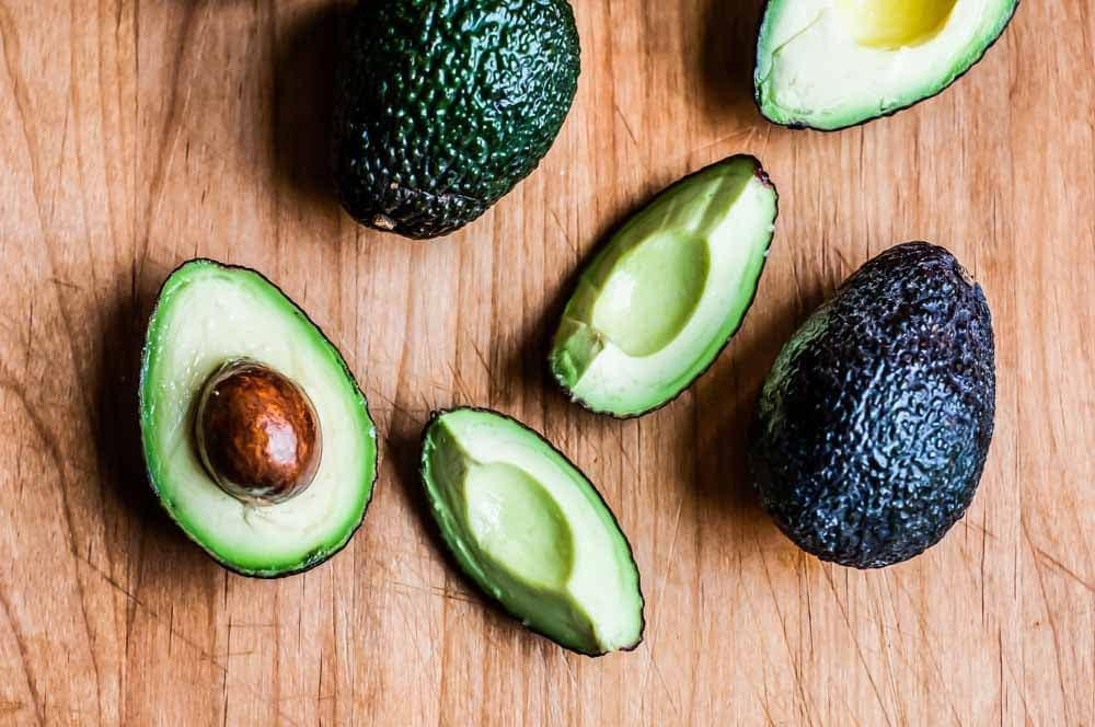sliced and whole avocados, a healthy fat and on my list of brain healthy foods, as one of the best brain food ingredients to add to a smoothie.