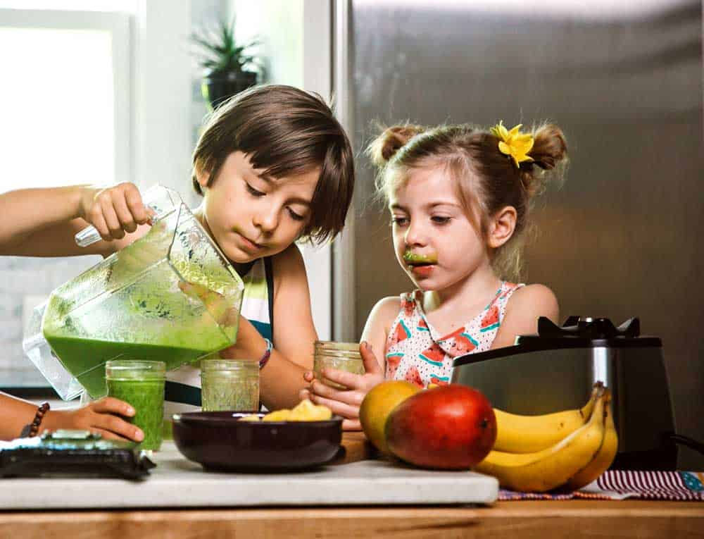 two kids pouring a green smoothie for kids