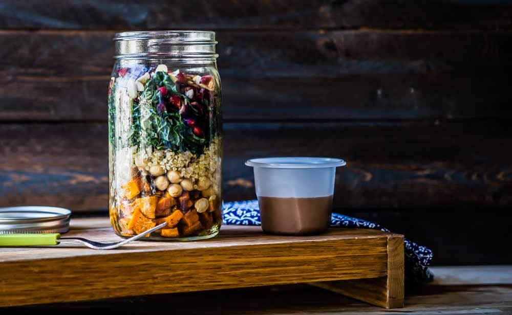 a fully layered mason jar salad with a homemade dressing next to it, ready to go