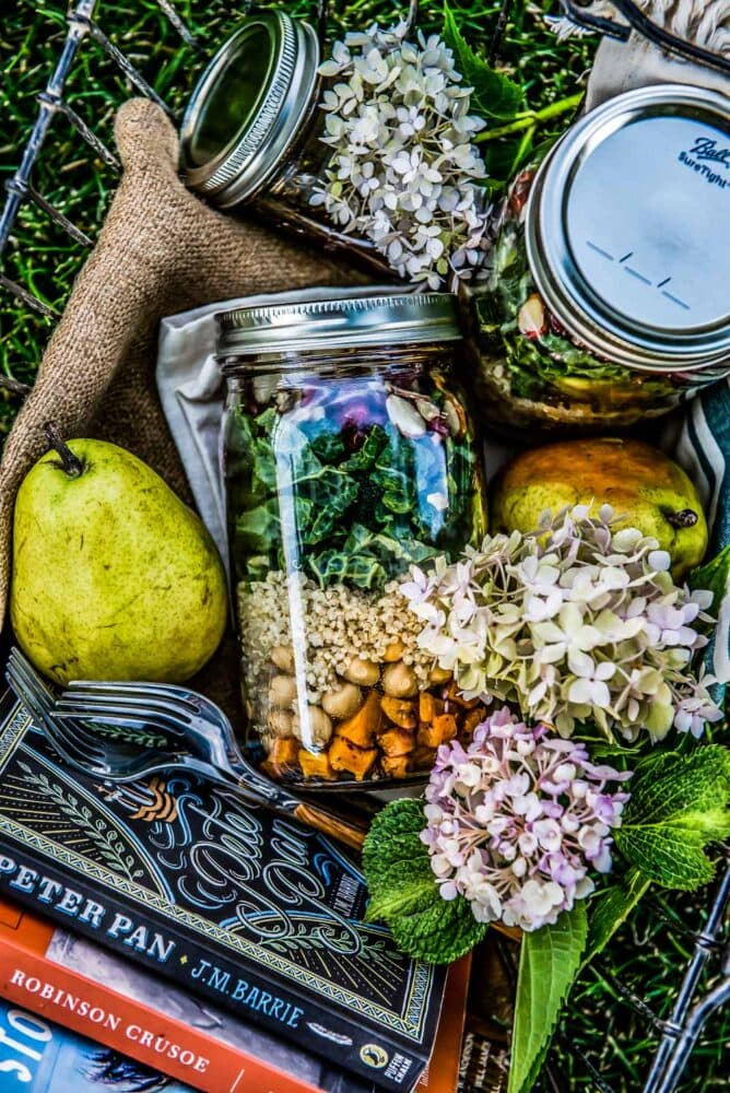 picnic basket of layered mason jar salad recipe complete with butternut squash, quinoa, kale, pomegranate, and sliced almonds.