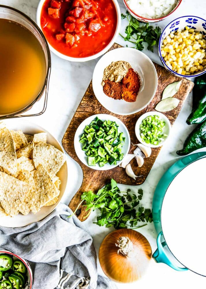 all the ingredients + toppings needed for a tortilla soup recipe
