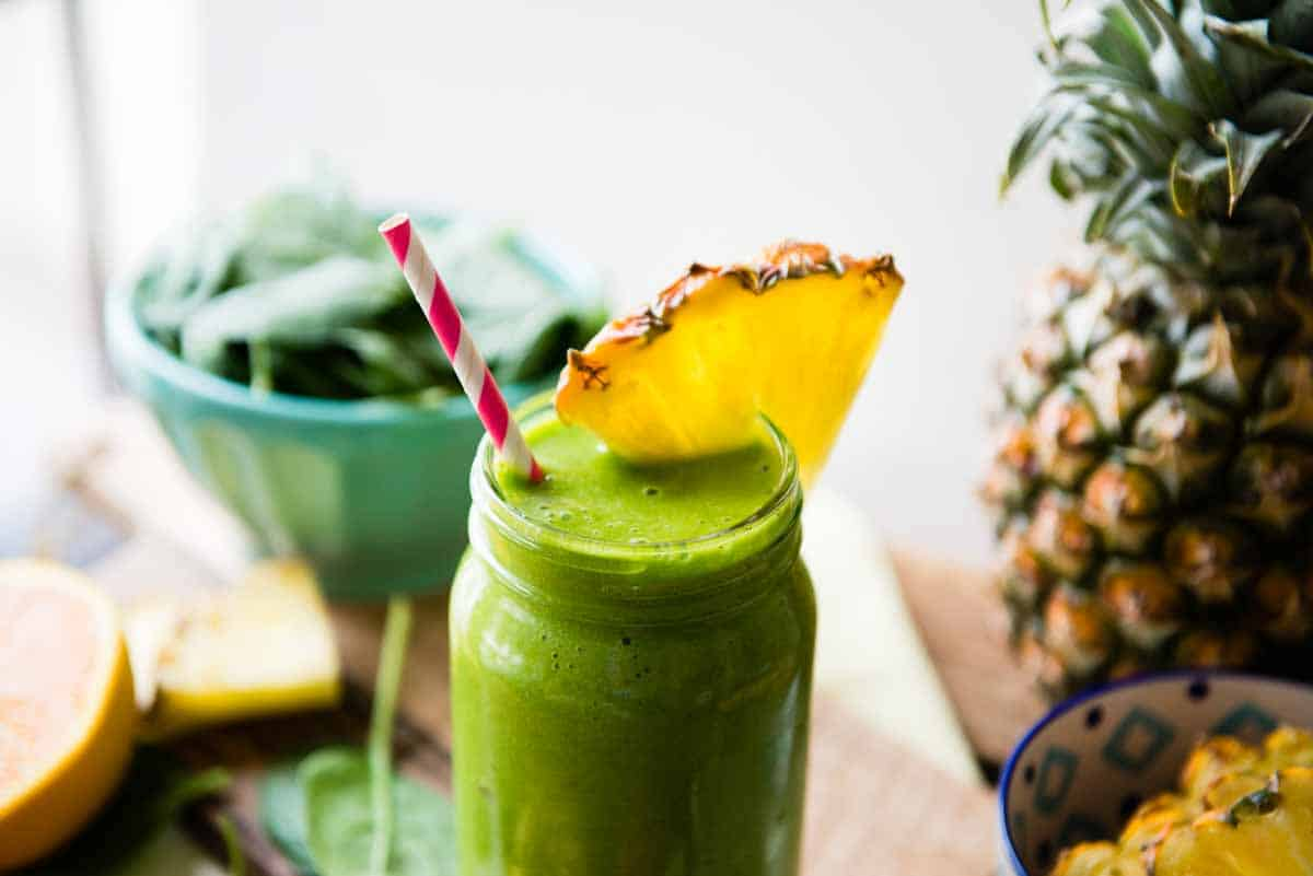 Green smoothie in mason jar with paper straw