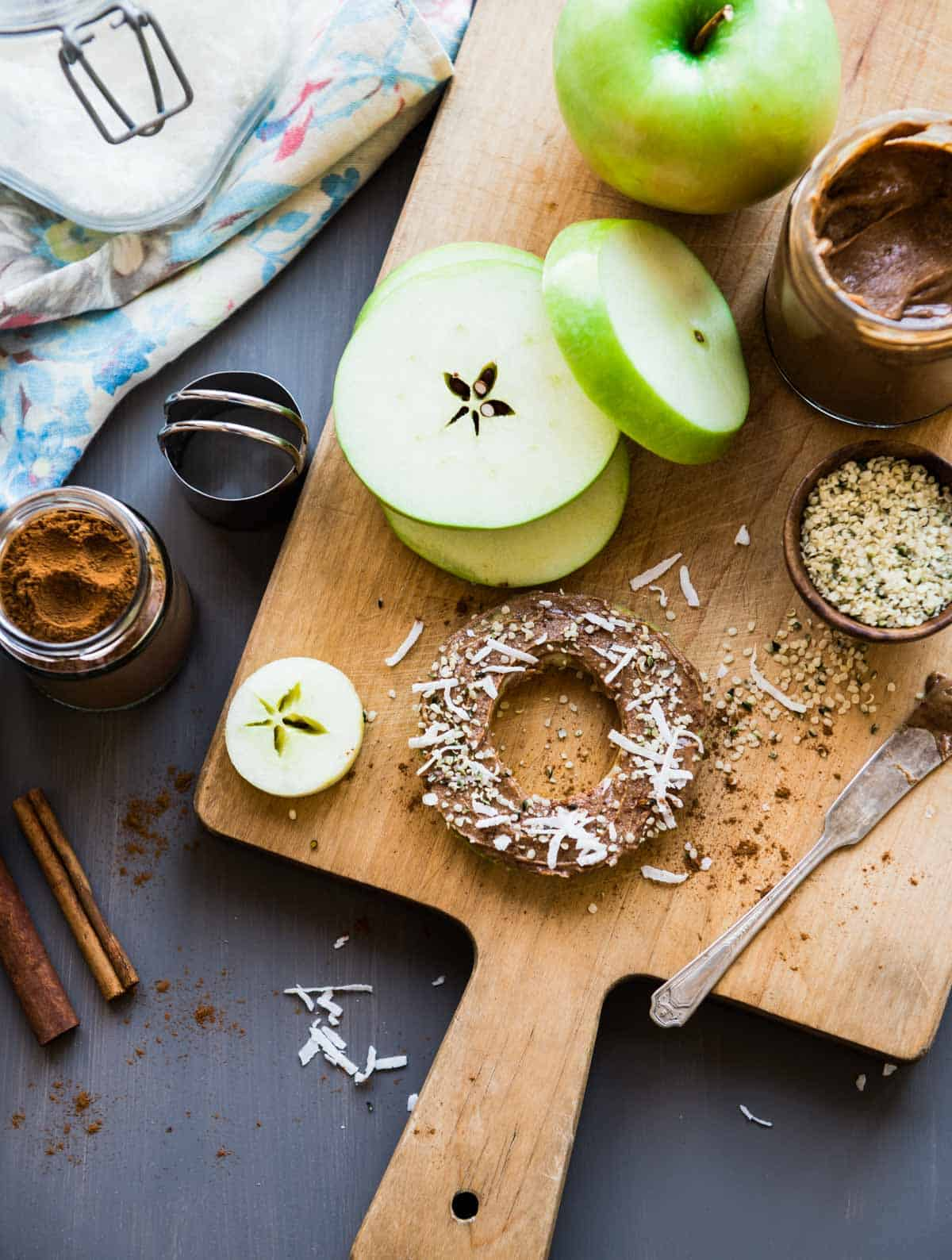 Green apples sliced on a cutting board with almond butter and hemp hearts